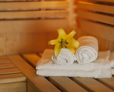 Close up fresh towels and yellow lily in sauna