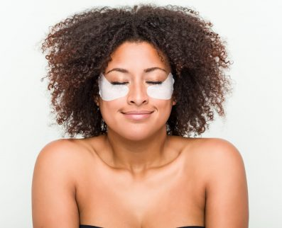 Close up of a young african american woman with an eye skin treatment
